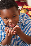 8 year old boy holding up pile of coins near chin vertical