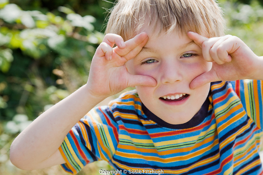 On a hot summer day outing, a playful boy mimics the photographer.