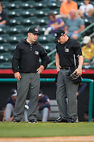 Umpires Matt Carlyon (left) and Ryan Powers chat between innings of the South Atlantic League game between the Rome Braves and the Hickory Crawdads at L.P. Frans Stadium on May 12, 2016 in Hickory, North Carolina.  The Braves defeated the Crawdads 3-0.  (Brian Westerholt/Four Seam Images)