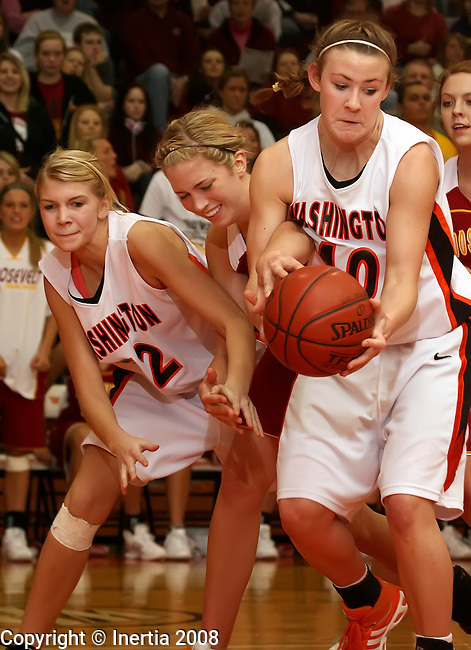 SIOUX FALLS, SD - January 13:  Anne Aamlid #35 of Roosevelt reaches her hand in to hold the ball as Ashley Eide #40 of Washington takes it away in the second half of their GDC game Tuesday night at Washington. Also pictured for Washington is Mercede Stotesber #52. (Photo by Dave Eggen/Inertia)