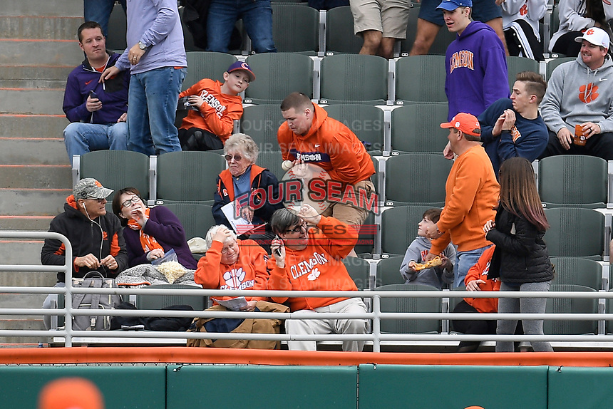 A fan in the left field stands can't make a catch on a home run ball hit by South Alabama's Ethan Wilson in a game against the Clemson Tigers on Opening Day, Friday, February 15, 2019, at Doug Kingsmore Stadium in Clemson, South Carolina. Clemson won, 6-2. (Tom Priddy/Four Seam Images)