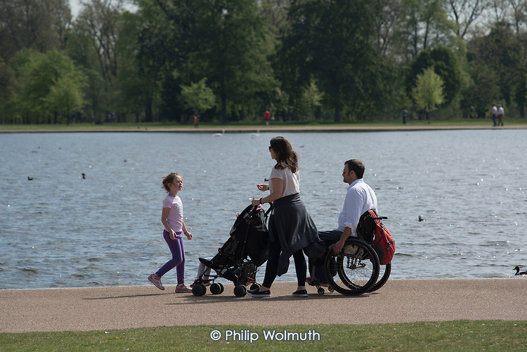 Family with a pushchair and wheelchair, Kensington Gardens, London.