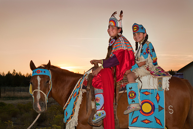 Native American family of two sisters dressed in traditional clothing and beadwork ride the family's horse while tacked up with traditional beadwork during sunset, Warm Springs Indian Reservation, Oregon.