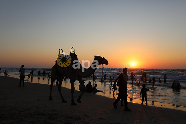 Palestinians enjoy their time at the beach of Deir al-Balah sea, in the center of Gaza Strip, during a hot day on August 11, 2021. The beach is one of the few open public spaces in this densely populated city. Photo by Ashraf Amra
