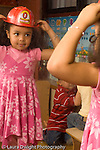 Preschool New York City ages 4-5 girl in dressup fire hat looking at self in mirror vertical
