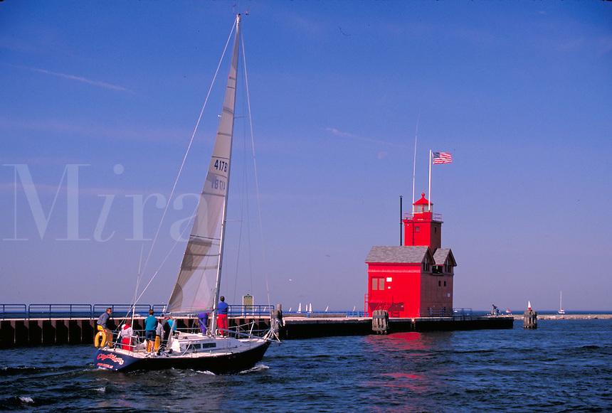 sailboat entering Lake Michigan, lighthouses. Holland Michigan USA.