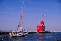 sailboat entering Lake Michigan, lighthouses. Holland Michigan USA.