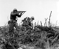 A Marine of the 1st Marine Division draws a bead on a Japanese sniper with his tommy-gun as his companion ducks for cover.  The division is working to take Wana Ridge before the town of Shuri.  Okinawa, 1945.  S.Sgt. Walter F. Kleine.  (Marine Corps)<br /> Exact Date Shot Unknown<br /> NARA FILE #:  127-N-123170<br /> WAR & CONFLICT BOOK #:  1228