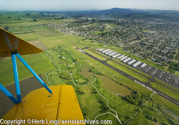 aerial photograph of the Petaluma Municipal Airport (O69) and part of Rooster Run golf course, Petaluma, Sonoma County, California from a Stearman.  Mount Tamalpais in Marin County is in the background.
