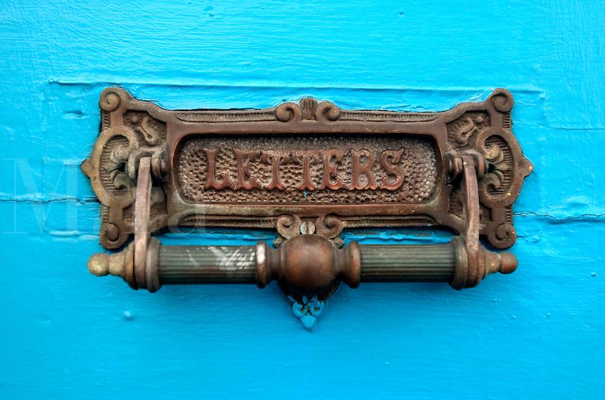 A mail slot on a blue doo