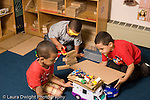 Preschool ages 3-5 three boys playing in block area with toy tools vehicles and human figures horizontal