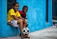 Brazil, Rio de Janeiro, Rio de Janeiro, Brazilian children with a football in the street of a favela