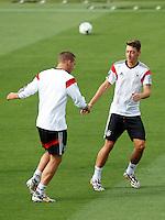 Mesut Ozil and Lukas Podolski of Germany warming up during training