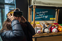 Switzerland. Canton Ticino. Lugano. Main Post office. Post finance. A young woman is playing a game with a virtual reality headset which is a head-mounted device providing virtual reality for the wearer. Virtual reality (VR) headsets are widely used with video games but they are also used in other applications, including simulators and trainers. They comprise a stereoscopic head-mounted display (providing separate images for each eye). 22.02.2019 © 2019 Didier Ruef