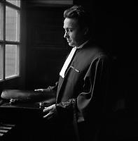 """8 juin 1961. Plan taille de Maître Souquière (avocat de l'accusé Camille Ajustron) en tenue, vue de profil, tient dans ses mains sa serviette (sacoche). Cliché pris dans le cadre de l'affaire de la """"Tournerie des drogueurs"""" dont le procès s'est ouvert à Toulouse le 5 juin 1961. Observation: Affaire de la """"Tournerie des drogueurs"""" : Procès qui s'est ouvert aux assises de Toulouse le 5 juin 1961, sous la présidence de M. Gervais (conseiller doyen). Sur le banc des accusés se trouvent François Lopez, Raoul Berdier, Marie-Thérèse Davergne (Maïté) et d'autres malfaiteurs toulousains (Camille Ajestron, Henri Oustric, Raymond Peralo, Marcel Filiol, Paul Carrère, Charles Davant et François Borja). Outre les accusations pour association de malfaiteurs, ils comparaissent pour l'assassinat de Jean Lannelongue, propriétaire du Cabaret la Tournerie des Drogueurs (rue des Tourneurs) dans la nuit du 3 au 4 janvier 1959, au cours d'une tentative de racket."""