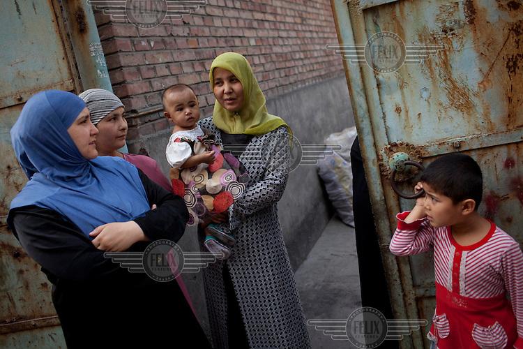 Uighur women stand outside in their neighbourhood in Urumqi.