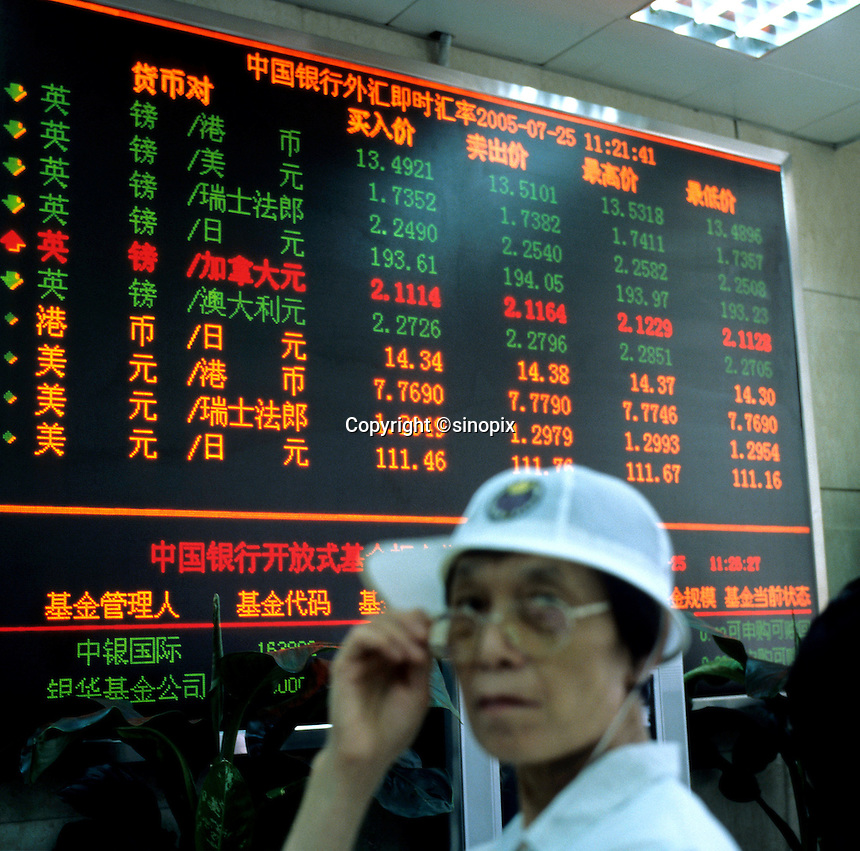An elder woman sits in front of a foreign exchange rate index at a bank in Beijing, China..