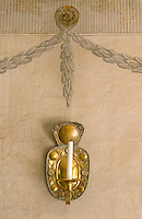 A hand-painted laurel garland above a brass wall sconce