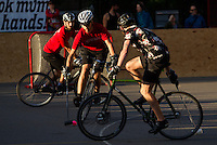 17 AUG 2014 - LONDON, GBR - A player from Mondial (in red and black) tries to find a way past a Triple Jay opponent (in black) during the 2014 London Open bike polo tournament final in Highbury Fields in London, Great Britain (PHOTO COPYRIGHT © 2014 NIGEL FARROW, ALL RIGHTS RESERVED)