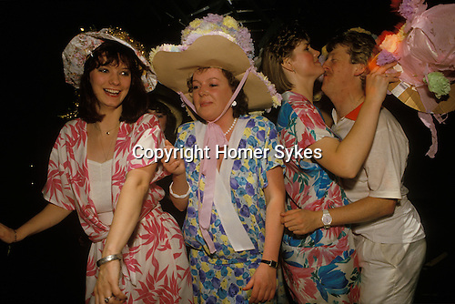 Birmingham, West Midlands. 1980's<br /> In a pre-wedding ritual at the Millionaires Club each Thursday night, girls that are getting married the coming Saturday, traditionally wear a floral dress and a straw bonnet decorated with paper flowers.  Many bring family photo albums to show their group of invited friends. It's one last chance to have a fling with an old boyfriend. Get tipsy, recover on Friday and get married on Saturday.