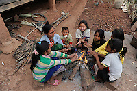 LAOS province Oudomxay , village Houyta, ethnic group Khmu, family share the warmth at fire place / LAOS Provinz Oudomxay Dorf Houyta , Ethnie Khmu , Familie waermt sich gemeinsam am Feuer