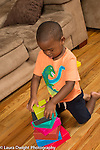 Three year old boy at home kneeling, building stack of rectangular colored blocks