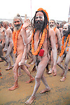 A Naga sadhu carries his mobile phone in a red pouch in the parade down to the riverbank to take a holy bathe.