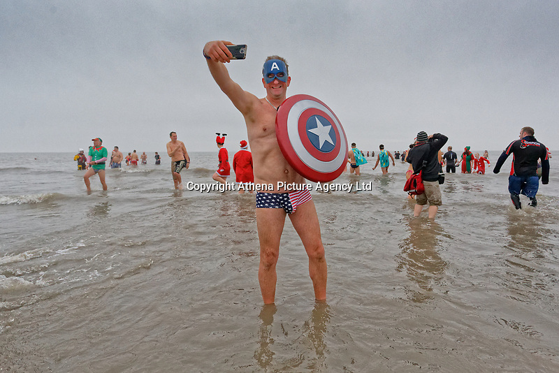 Pictured: A man dressed as Captain America takes a selfie. Tuesday 25 December 2018<br /> Re: Hundreds of people take part in this year's Porthcawl Christmas Swim in south Wales, UK.
