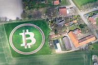 Bitcoin Zeichen auf einem Feld mit Tracktor: EUROPA, DEUTSCHLAND,  NIEDERSACHSEN (EUROPE, GERMANY), 23.04.2021: Bitcoin Zeichen auf einem Feld mit Tracktor