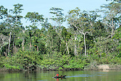 Aldeia Baú, Para State, Brazil. Kayapo man wearing a red t-shirt paddling a dugout canoe on the Curua River.