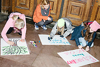 People make signs in a doorway of the Smithsonian Institution Building (The Castle) as people gather in the National Mall area of Washington, DC, for the Women's March on Washington protest and demonstration in opposition to newly inaugurated President Donald Trump on Jan. 21, 2017.