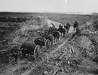 NLS Haig - Artillery going through a cutting in the Canal du Nord.<br /> <br /> 18 pounder field gun and its limber being towed by the standard 6 horses, passing through a cutting in the Canal du Nord, France. A driver is mounted on each of the 3 leftside horses. The gun's No 1, a Sergeant, rides ahead. On top of the gun is stowed its portable camouflage netting.