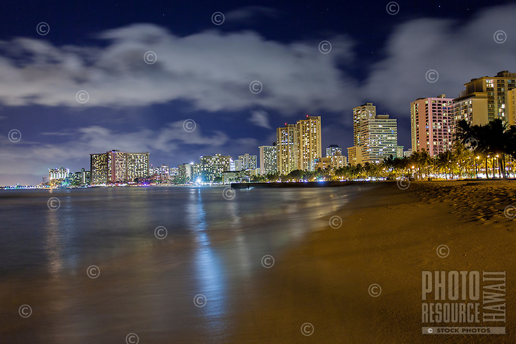 The Waikiki skyline at night, with lights from hotels reflecting off the water, as seen from Queen's Beach, Waikiki, O'ahu.