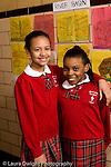 K-8 Parochial School Bronx New York Grade 4 portrait of two girls in hallway differing heights vertical
