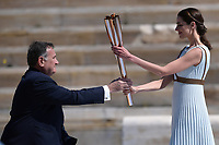 19th March 2020, Athens, Greece; The Olympic Flame, lit on Mount Olympia, is handed over officially to the  congregation from Japan, to be taken to Tokyo for the 2020 Olympic Games in July 2020. President of the Hellenic Olympic Committee SpyrCapralosL receives the Tokyo Olympic Flame torch from Greek actress Xanthi Georgiou who was playing the role of an ancient Greek High Priestess at the handover ceremony held at the Panathenaic stadium, in Athens