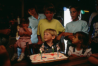 """Candles are lit on the cake and his family surrounds Jake Colson while singing """"Happy Birthday."""""""