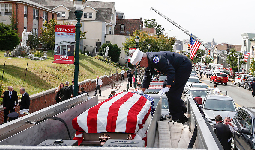 Former Manasquan fire chief Ed Hill secures the flag-draped casket containing the remains of longtime volunteer firefighter Dan McCann after McCann's funeral mass in Kearny. McCann died last week after a fire department training exercise.  9/21/16  (Andrew Mills | NJ Advance Media for NJ.com)
