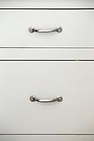 Inox handles on white drawers