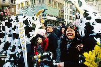 Switzerland. Basel. Fasnacht Carnival. A couple of  cows are in the streets among the crowd. One cow is a man disguised, the other is made out of carboard and synthetic resine and was elected Miss Fasnacht Carnival. A laughing woman holds flowers in her hand.  © 1997 Didier Ruef