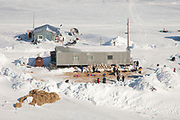 Aerial view of teams resting on straw outside the National Guard Armory building and temporary Iditarod Headquarters at Shaktoolik checkpoint in Arctic Alaska during the 2010 Iditarod