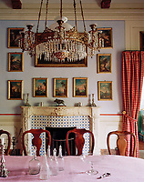 Classic Delft tiles decorate the fireplace in the dining room. The formality of the room is broken by a simple checked curtain.