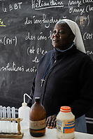 NIGER Zinder, school of catholic church , order sister in chemistry class / NIGER Zinder, Projekte der katholischen Kirche, Sr. Honorine, Schwester aus Togo, Schulleiterin St. Joseph College, Chemie Klasse