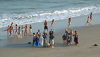 A couple is married on the beach as kids run past at Virginia Beach, Va.