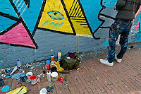 A Colombian artist paints graffiti on the wall in La Candelaria, Bogota, 10 July 2010.