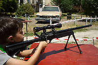 """Romania. Iași County. Iasi. Filip, an eight years old boy, is shooting with an air gun during the festival """" Street Delivery. Global Warning"""" which takes place in the Pogor garden near the the museum """"Vasile Pogor"""", a literary history museum which is part of the Iași Romanian Literature Museum ( Muzeul Literaturii Romane Iasi). The air gun is a replica of a sniper rifle and shoots 6mm Plastic Airsoft BB's using the spring powered bolt action. The ASG AW .308 Airsoft Sniper Rifle has an all metal barrel and bolt assembly with a polymer stock. A memorial with a Californian Dodge car which used to belong to the romanian poet Mihai Ursachi (1941-2004). The poet brought back the car from his exile in the USA in 1991 after the romanian revolution. An air gun (often called pellet gun or BB gun depending on the projectile) is any variety of pneumatic weapon that propels projectiles by means of compressed air or other gas. Iași (also referred to as Iasi, Jassy or Iassy) is the largest city in eastern Romania and the seat of Iași County. Located in the Moldavia region, Iași has traditionally been one of the leading centres of Romanian social, cultural, academic and artistic life. The city was the capital of the Principality of Moldavia from 1564 to 1859, then of the United Principalities from 1859 to 1862, and the capital of Romania from 1916 to 1918. 14.06.15 © 2015 Didier Ruef"""