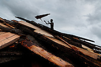 A Colombian worker, throwing a wood cutoff, walks on a pile of boards at a sawmill in Tumaco, Colombia, 17 June 2010. Tens of sawmills located on the banks of the Pacific jungle rivers generate almost half of the Colombia's wood production. The wood species processed here (sajo, machare, roble, guabo, cargadero y pacora) are mostly used in the construction industry and the paper production. Although the Pacific lush rainforest in Colombia is one of the most biodiverse area of the world, the region suffers an extensive deforestation due to the uncontrolled logging in the last years.