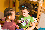 Education Preschool 3-4 year olds two children talking in kitchen pretend play area horizontal