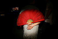 CHINA. Beijing. A man holding a fan whilst watching the opening ceremony of the Beijing Summer Olympics. 2008