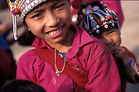 Laos, Luang Namtha Province, Ban Nammat Gao village..Young Akha girl, kid on back..Photo by Kees Metselaar, 2003