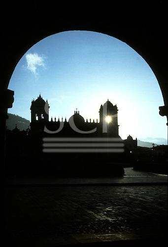 Cusco, Peru. Plaza de Armas through an arch with the sun behind the cathdral.